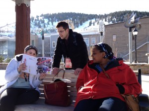 Maggie Woodward, Leah Railey, and Dillon Ward studying the Sundance program while waiting for the Theater Loop shuttle at the Main Street depot in Park City, Utah.
